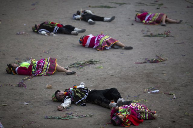 In this Sunday, March 29, 2015 photo, performers from the Huanta district of Ayacucho lie on the ground representing the victims of a massacre that took place during the years of the country's political violence, during the Vencedores de Ayacucho dance festival, in the Acho bullring in Lima, Peru. The Ayacucho region in the Peruvian Andes saw some of the worst modern-day atrocities in Peru, with more than 8,000 believed killed in that region alone in violence from 1980 to 2000 between Shining Path rebels and government forces. (Photo by Rodrigo Abd/AP Photo)