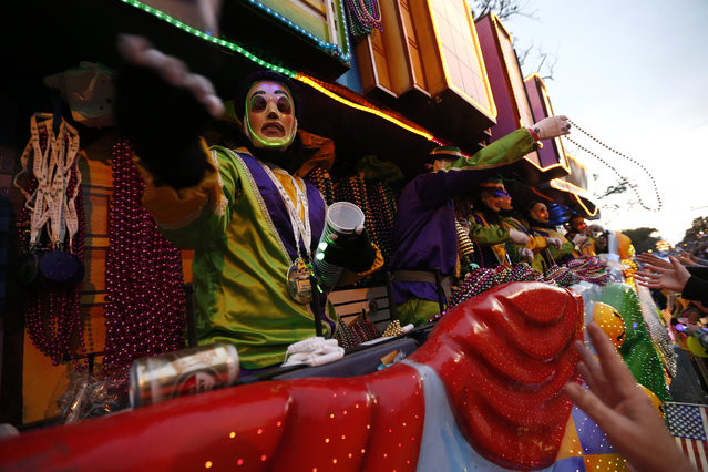 A rider throws beads as the Krewe of Endymion Mardi Gras parade rolls through New Orleans, Saturday, February 6, 2016. (Photo by Gerald Herbert/AP Photo)