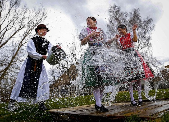 A man throws water on two women as part of traditional Easter celebrations in Szenna, Hungary on April 3, 2015. (Photo by Laszlo Balogh/Reuters)