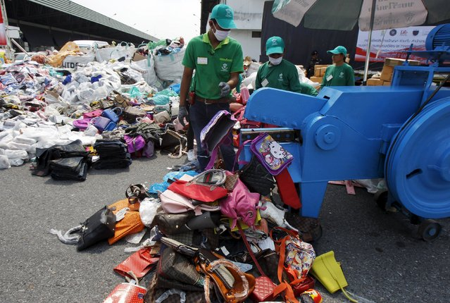 Thai Department of Intellectual Property and police officials destroy counterfeit goods at Khlongluang Transportation Station in Pathumtani province, on the outskirts of Bangkok April 9, 2015. The counterfeit goods, which included piles of CDs, DVDs, handbags, clothes, brand name shoes, cell phones, caps, glasses, computers, cosmetics and watches are worth over 3.7 billion Thai baht ($ 115,790,901), according to local authorities. (Photo by Chaiwat Subprasom/Reuters)