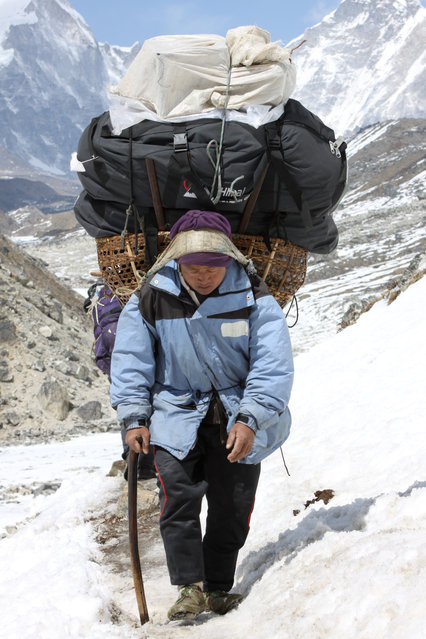 A porter walks along a trail carrying a load belonging to trekkers returning from Everest Base Camp, at Thuglha Pass, Nepal, Friday, April 10, 2015. According to reports in the state run China Daily, a proposed plan for a rail link from China to Nepal could involve boring a tunnel under the 8,850-meter (29,035-foot) Mount Everest. The building of a rail link from Chinese-controlled Tibet to Nepal would need to pass beneath the Himalayan mountain range, according to reports. (Photo by Tashi Sherpa/AP Photo)