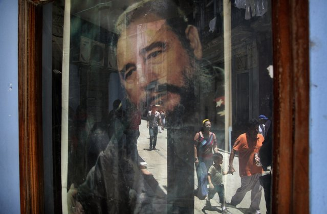In this May 15, 2015 file photo, pedestrians are reflected in a post office window where a poster of Fidel Castro hangs in Havana, Cuba. (Photo by Desmond Boylan/AP Photo)