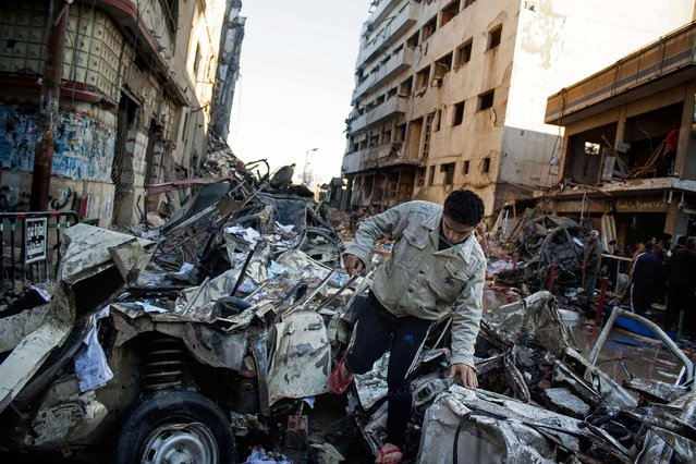"""A man makes his way through rubble at the scene of an explosion at a police headquarters building that killed at least a dozen people, wounded more than 100, and left scores buried under the rubble, in the Nile Delta city of Mansoura, Egypt, on December 24, 2013. The country's interim government accused the Muslim Brotherhood of orchestrating the attack, branding it a """"terrorist organization."""" (Photo by Ahmed Ashraf/Associated Press)"""