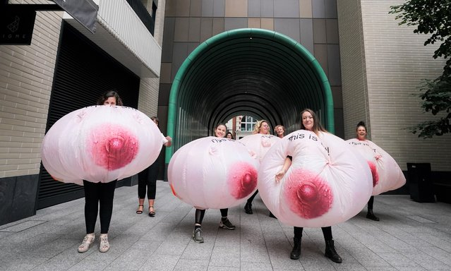 Protesters wearing inflatable breasts stand outside Facebook's headquarters in central London on Wednesday September 1, 2021, to complain about the social media giant's images algorithm. The aim of the event is for all medical tattoo artists and breast cancer survivors to be able to freely post images without the pictures being removed and the accounts blocked. (Photo by Ian West/PA Images via Getty Images)
