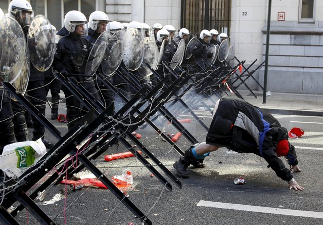 A demonstrator shows his bottom to riot police during a protest by European workers and trade union representatives to demand better job protection in the European Union countries in Brussels, in this March 24, 2011 file photo. (Photo by Thierry Roge/Reuters)