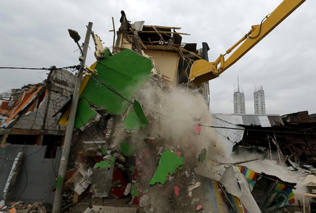 An excavator demolishes buildings at Kalijodo red-light district in Jakarta, Indonesia, February 29, 2016. (Photo by Reuters/Beawiharta)