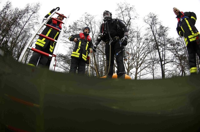 Martin Weitzendoerfer, diver of Frankfurt's firefighter rescue brigade, leaves a frozen lake during a rescue exercise in Frankfurt, Germany, January 24, 2017. (Photo by Kai Pfaffenbach/Reuters)