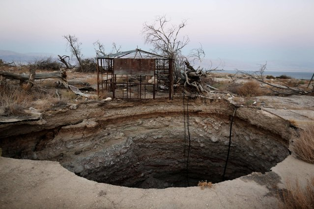 A general view shows a sinkhole in Israel's abandoned tourist resort of Ein Gedi on the shore of the Dead Sea on July 11, 2016. Experts have warned that the Dead Sea, the lowest and saltiest body of water in the world, is on course to dry out by 2050, with the emergence of sinkholes forcing the closure of roads and beaches, as well as damaging agriculture. (Photo by Menahem Kahana/AFP Photo)