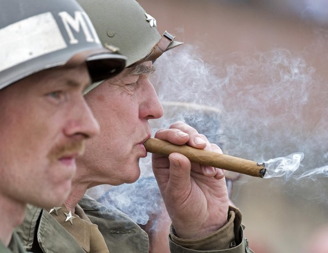 Amateur actors dressed in historical US Uniforms re-enact the link-up of Soviet and American troops during the 70th anniversary of the Elbe Day in Torgau, eastern Germany, Saturday, April 25, 2015. (Photo by Jens Meyer/AP Photo)