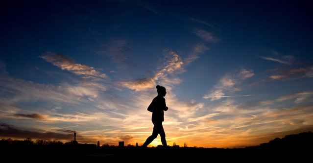 A jogger is silhouetted against the morning sky during sunrise in Hannover, northern Germany, January 3, 2014. (Photo by Julian Stratenschulte/AP Photo/DPA)