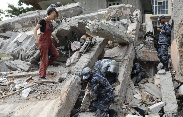 An unidentified tourist (L) stands as members of a rescue team search for victims under the rubble of a tourist's hotel in Thamel, a tourist hub in Kathmandu, during early morning a day after a massive earthquake, Kathmandu, Nepal, 26 April 2015. (Photo by Narendra Shrestha/EPA)