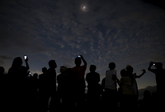 People watch and take pictures of the solar eclipse at the beach on Ternate island, Indonesia, March 9, 2016. (Photo by Reuters/Beawiharta)