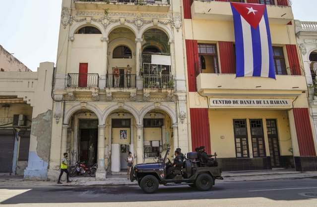 Special forces police patrol the streets as they drive past a large Cuban flag hanging from the facade of a building, in Havana, Cuba, Wednesday, July 21, 2021. (Photo by Eliana Aponte/AP Photo)