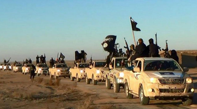 In this undated file photo released online in the summer of 2014 on a militant social media account, which has been verified and is consistent with other AP reporting, militants of the Islamic State group hold up their weapons and wave its flags on their vehicles in a convoy on a road leading to Iraq, in Raqqa, Syria. (Photo by Militant photo via AP Photo)