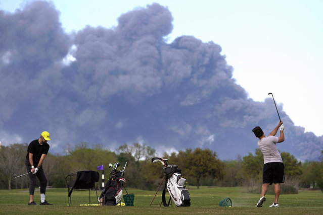 Golfers practice at the Battleground Golf Course driving range as a chemical fire at Intercontinental Terminals Company continues to send dark smoke over Deer Park, Texas, Tuesday, March 19, 2019. (Photo by Melissa Phillip/Houston Chronicle via AP Photo)