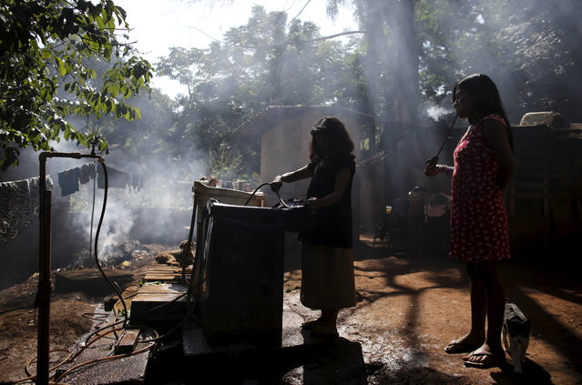 A Guarani Indian woman fills a pot with water as her daughter (R) looks on in the village of Pyau at Jaragua district, in Sao Paulo April 28, 2015. (Photo by Nacho Doce/Reuters)