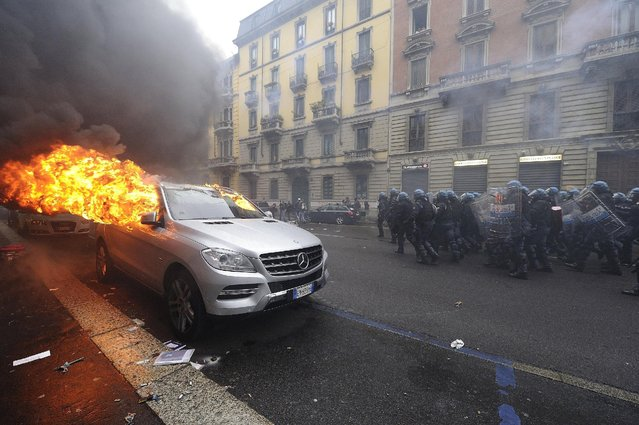 Italian anti-riot policemen run in front of a burning car during a rally against Expo 2015 in Milan, Italy, May 1, 2015. (Photo by Flavio Lo Scalzo/Reuters)