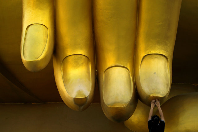 A woman prays while touching the fingers of a Buddha statue during the annual Makha Bucha Day, which celebrates Buddha's teachings, in Ang Thong, Thailand February 11, 2017. (Photo by Jorge Silva/Reuters)