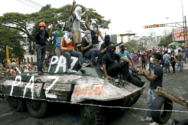 Opposition supporters stand over a monument of a tank which they dragged into the middle of the street during a protest against Nicolas Maduro's government in San Cristobal, some 410 miles (660 km) southwest of Caracas February 19, 2014. Tensions have risen in Venezuela since Lopez, a 42-year-old Harvard-educated economist, surrendered to troops on Tuesday after spearheading three weeks of often rowdy demonstrations against President Nicolas Maduro's government. (Photo by Carlos Eduardo Ramirez/Reuters)