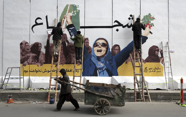 In this March 8, 2019 file photo, an independent Afghan artists draws graffiti on a barrier wall of the Ministry of Women's Affairs to mark International Women's Day, in Kabul, Afghanistan. In a Thursday, March 28, 2019 report the Special Inspector General for Afghan Reconstruction, a U.S. watchdog, said that Afghanistan will remain dependent on international donors and foreign help even after a peace deal with the Taliban is reached. The report identified main high-risk areas including threats to women's rights. (Photo by Rahmat Gul/AP Photo)