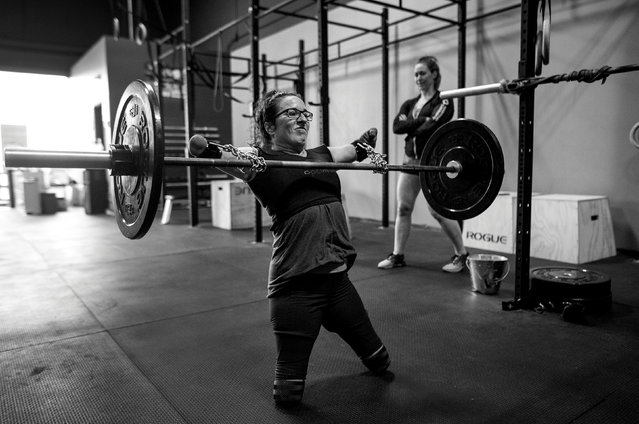 """With the aid of chains purchased at the hardware store and deadlift straps, Lindsay performs cleans under the watchful eye of her coach Jenny Jeffries. """"It's been an important relationship for me"""", says Jeffries, who was admittedly affected by her mother's disabilities following a car accident. """"How could it not – seeing Lindsay doing what she's been doing her whole life"""". (Photo by Darren Calabrese/Reuters/Courtesy of World Press Photo Foundation)"""