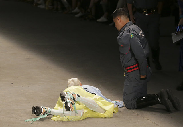 Model Tales Soares lies on the catwalk as a paramedic tends to him after he collapsed during Sao Paulo Fashion Week in Sao Paulo, Brazil, Saturday, April 27, 2019. A statement from organizers said that Soares died after taking ill while participating in the Sao Paulo's Fashion Week. (Photo by Leco Viana/Thenews2 via AP Photo)