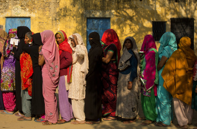Indian women stand in a queue to cast their votes at a village near Amroha in Uttar Pradesh, India, Wednesday, February 15, 2017. Uttar Pradesh and four other Indian states are having state legislature elections in February-March, a key mid-term test for Prime Minister Narendra Modi's Hindu nationalist government which has been ruling India since 2014. (Photo by Manish Swarup/AP Photo)
