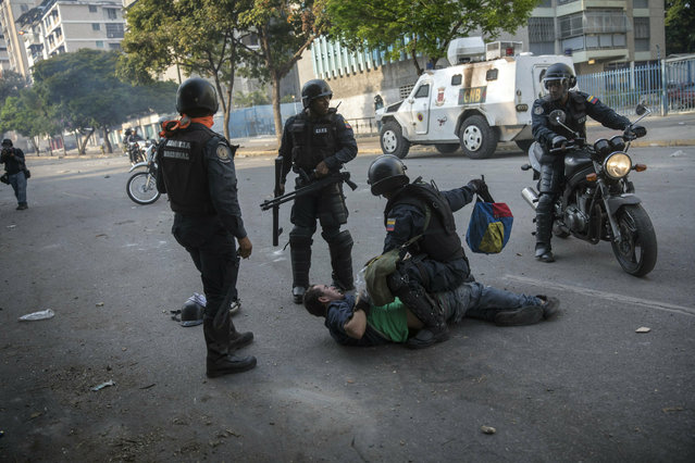 National Police detain an anti-government protester near the La Carlota airbase during clashes between the two sides in Caracas, Venezuela, Wednesday, May 1, 2019. (Photo by Rodrigo Abd/AP Photo)