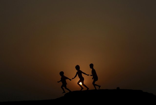Children are silhouetted against the setting sun as they play on a ground on the outskirts of Agartala, capital of India's northeastern state of Tripura, April 23, 2015. (Photo by Jayanta Dey/Reuters)