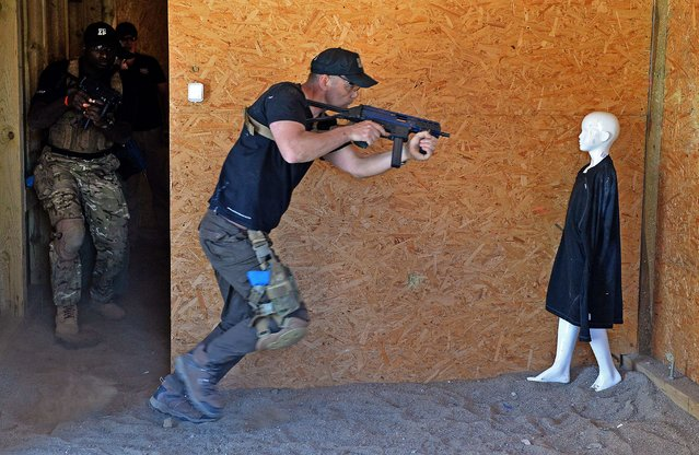 A security operative fires at a mannequin within a replica of part of the Somali capital Mogadishu during a training at Poland's private European Security Academy (ESA) on April 24, 2015 in Wlosciejewki, Poland. The private bootcamp prepares people from around the world for missions in danger zones. (Photo by Janek Skarzynski/AFP Photo)