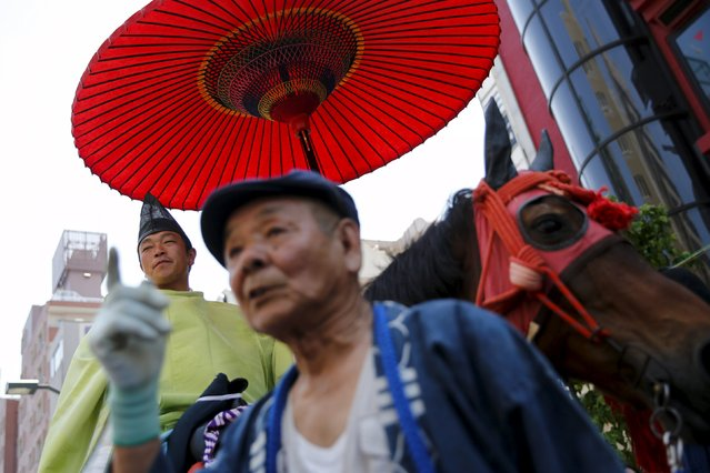 A man wearing a Shinto dress rides a horse during the Sanja Matsuri festival in the Asakusa district of Tokyo May 17, 2015. (Photo by Thomas Peter/Reuters)