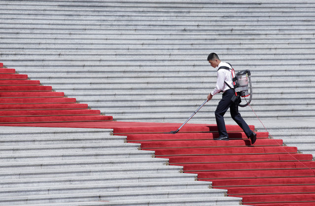 A staff member cleans the red carpet in front of the Great Hall of the People in Beijing, China, May 27, 2019. (Photo by Jason Lee/Reuters)