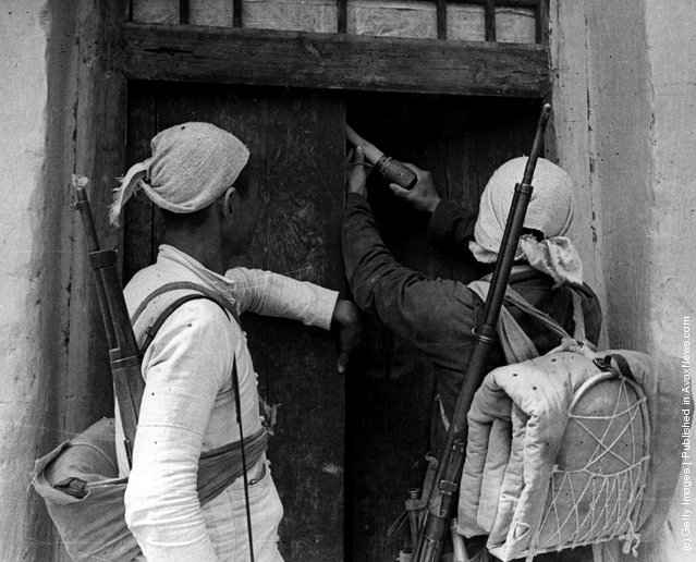 1944: Two Chinese Red Army militia men plant a potato masher grenade in a farmer's doorway as a killer trap