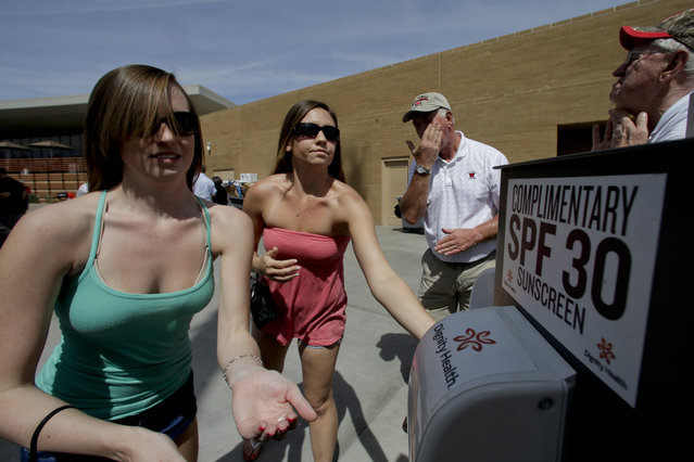 Ashleigh Vincent, left, and Tara Gregory rub out a sunscreen on the first day of spring before a spring exhibition baseball game between the Colorado Rockies and the Milwaukee Brewers in Scottsdale, Ariz., Thursday, March 20, 2014. (Photo by Chris Carlson/AP Photo)