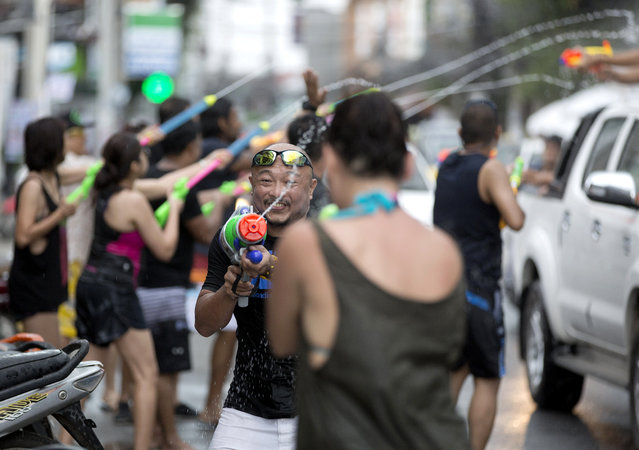 In this April 13, 2015 file photo, tourists and locals exchange water pistol fire during the Songkran festival to celebrate the Thai New Year on Samui Island in Surat Thani province, Thailand. Thailand's military government is putting a dampener on the annual nationwide water fight. Despite Thailand's worst drought in 20 years, the junta says it has no intention of limiting the virtually around-the-clock water throwing that defines the three-day Songkran festival. Instead, it has decided to impose morality measures. (Photo by Mark Baker/AP Photo)