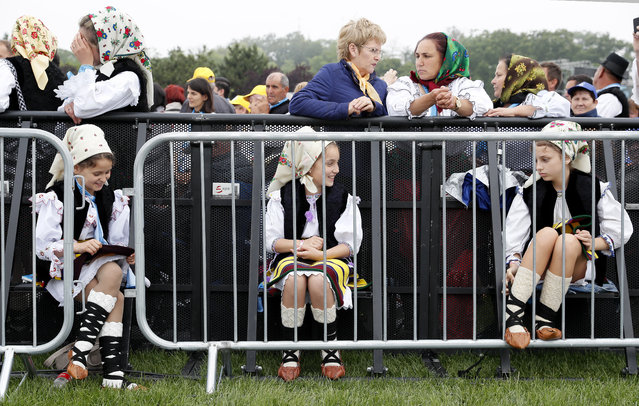 """Three Romanian girls, dressed in traditional attire, chat as they wait for the beatification mass held by Pope Francis at """"Campia Libertatii"""" field in Blaj, Romania, 02 June 2019. Pope Francis is on a three-day visit to Romania from 31 May to 02 June 2019. The pontiff visit takes place 20 years after Pope St. John Paul II's historic visit to Romania, having the motto """"Let's Walk Together"""". (Photo by Robert Ghement/EPA/EFE)"""