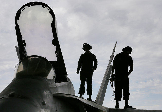 U.S. Marines work atop an F/A-18 at the 309th Aerospace Maintenance and Regeneration Group boneyard in Tucson, Ariz. on Thursday, May 21, 2015. The Marines are repairing F/A-18's to return to service at the 309th facility. (Photo by Matt York/AP Photo)