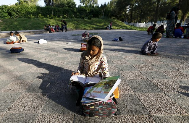 Children study between their classes at a local park in Islamabad April 22, 2015. Master Mohammad Ayoub, a Pakistani civil servant, started his program to educate underprivileged children in 1985. (Photo by Caren Firouz/Reuters)