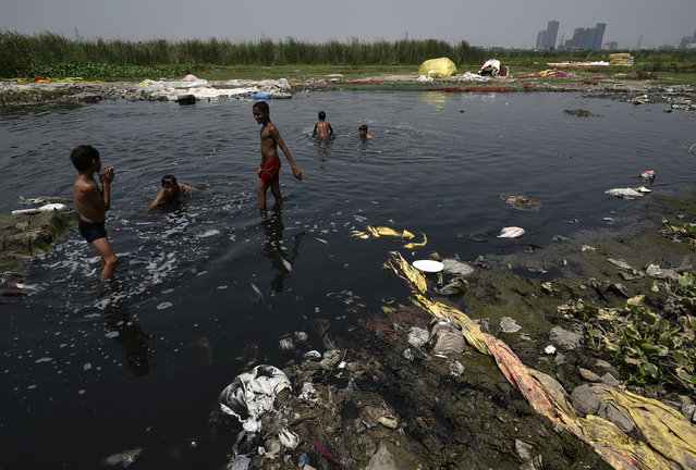 Children take bath in a dirty creek on the banks of Yamuna, near Okhla on June 4, 2019 in New Delhi, India. World Environment Day is marked anually on June 5. (Photo by Biplov Bhuyan/Hindustan Times via Getty Images)