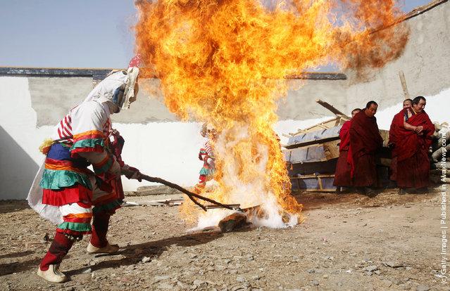 A lama burns a thing symbolizing evil spirits