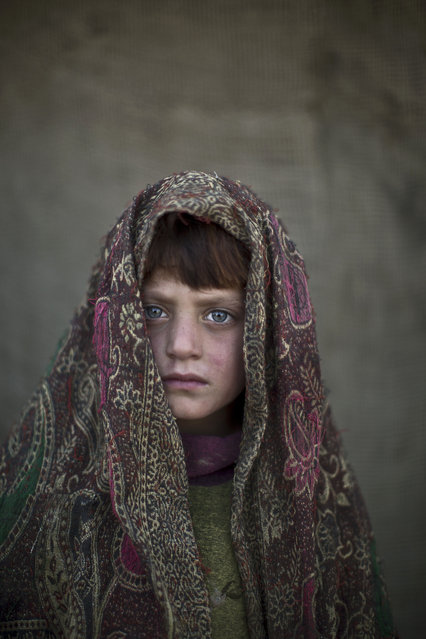 In this Friday, January 24, 2014 photo, Afghan refugee girl, Naseebah Zarghoul, 6, poses for a picture, while playing with other children in a slum on the outskirts of Islamabad, Pakistan. (Photo by Muhammed Muheisen/AP Photo)