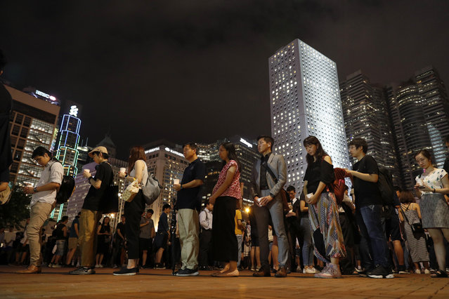"""Protesters join a candle light vigil for the fourth apparent suicide related to the protests against an extradition law to China in Hong Kong on Wednesday, July 10, 2019. It's still the world's """"freest"""" economy, one of the biggest global financial centers and a scenic haven for tycoons and tourists, but the waves of protests rocking Hong Kong are exposing strains unlikely to dissipate as communist-ruled Beijing's influence grows. (Photo by Vincent Yu/AP Photo)"""