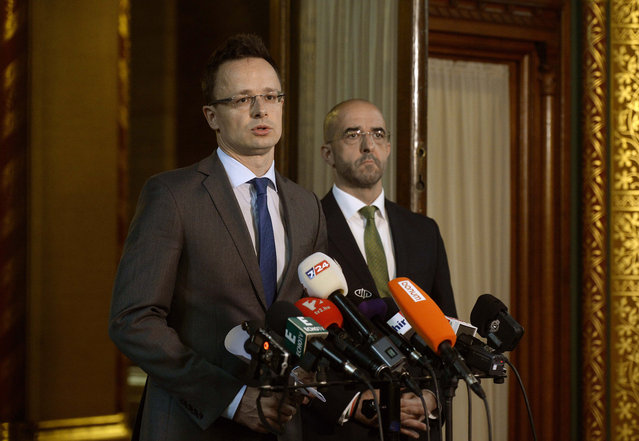 Hungarian Minister of Foreign Affairs and Trade Peter Szijjarto, left, speaks during a press conference to announce that the government has asked the interior minister to prepare the closure of the Hungarian Serbian border as government spokesman Zoltan Kovacs, right, looks on in the Parliament building in Budapest, Hungary, Wednesday, June 17, 2015. The Hungarian government plans to erect a 4-meter (13 feet)  high fence along the border with Serbia from where most of the migrants cross illegally the Hungarian border.  (Noemi Bruzak/MTI via AP)