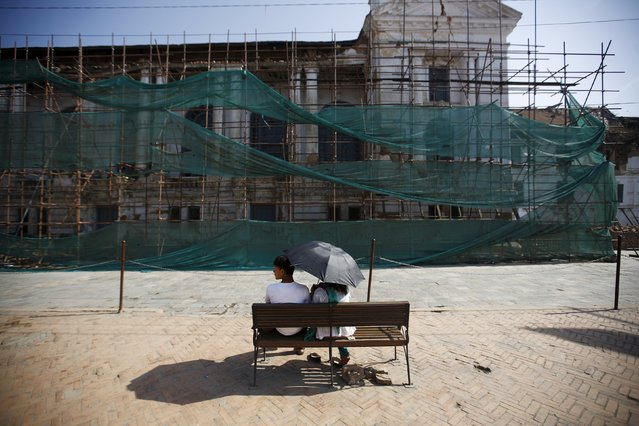 People sit in front of the damaged Bashantapur Durbar Square during the first anniversary of the earthquake in Kathmandu, Nepal, April 24, 2016. (Photo by Navesh Chitrakar/Reuters)