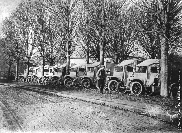 1915:  Ambulances during WW I parked under trees on a road in France