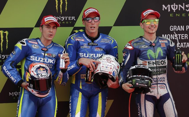 Aleix Espargaro of Spain and Team Suzuki MotoGP, center, poses on the podium after clocking the fastest time to take pole position for Sunday's race, next to second fastest time Spain's Maverick Vinales, left, and third fastest time Spain's Jorge Lorenzo in Montmelo, Spain, Saturday, June 13, 2015. The Catalunya Grand Prix will take place on Sunday in Montmelo. (AP Photo/Manu Fernandez)