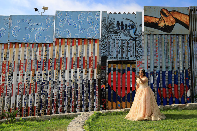 A girl poses in her quinceanera dress near the border fence between Mexico and U.S. in Tijuana, Mexico on  July 18, 2019. (Photo by Carlos Jasso/Reuters)