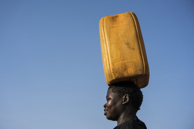 In this photo taken Wednesday, March 8, 2017, a young girl carries clean water home from a water treatment point built by UNICEF in Torit, South Sudan. (Photo by Mackenzie Knowles-Coursin/UNICEF via AP Photo)