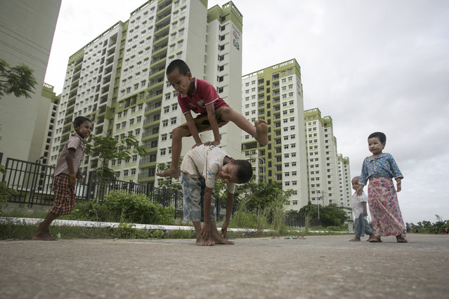 Children play near an apartment complex on the outskirts of Yangon, Myanmar on July 29, 2019. (Photo by Sai Aung Main/AFP Photo)
