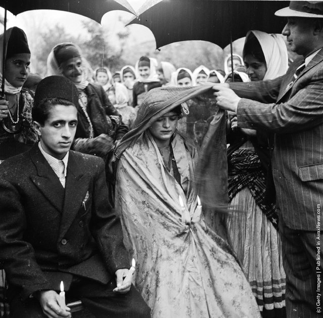 1952:  A Khan or feudal lord of a province lifts the veil from the face of a muslim bride in a village wedding ceremony. Her groom sits beside her with lit candles symbolising life